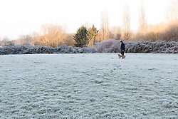 © Licensed to London News Pictures. 27/12/2016. Horsham, West Sussex, UK.  A man walks his dog on frost covered ground in Horsham, West Sussex. Parts of the south of England have woken to frost and freezing weather this morning.  Photo credit: Vickie Flores/LNP