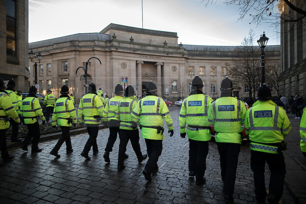 """© Licensed to London News Pictures . 26/11/2016 . Bolton , UK . Police move to separate anti-fascist protesters from the anti-mosque demonstrators ,  behind Bolton Town Hall . Approximately 100 people attend a demonstration against the construction of mosques in Bolton , under the banner """" No More Mosques """" , organised by a coalition of far-right organisations and approximately 150 anti fascists opposing the demonstration , in Victoria Square in Bolton Town Centre . Photo credit : Joel Goodman/LNP"""