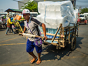 "15 FEBRUARY 2016 - ARANYAPRATHET, SA KAEO, THAILAND: A Cambodian porter in Aranyaprathet hauls a load of bottled water to the Cambodian side of the border. Thais selling bottled water in the border town of Aranyaprathet, opposite Poipet, Cambodia, have reported a surge in sales recently. Cambodian officials told their Thai counterparts that because of the 2016 drought, which is affecting Thailand and Cambodia, there have been spot shortages of drinking water near the Thai-Cambodian and that ""water shortages in Cambodia had prompted people to hoard drinking water from Thailand.""     PHOTO BY JACK KURTZ"