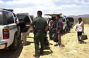 A U.S. Border Patrol agent rounds up a group of illegal immigrants from Mexico who sought relief from the scorching desert sun east of Sells, Arizona on the Tohono O'odham Nation.  The group walked for over two days in heat exceeding 110 degrees in an area known to have the highest death rate of illegal border crossers in the nation.