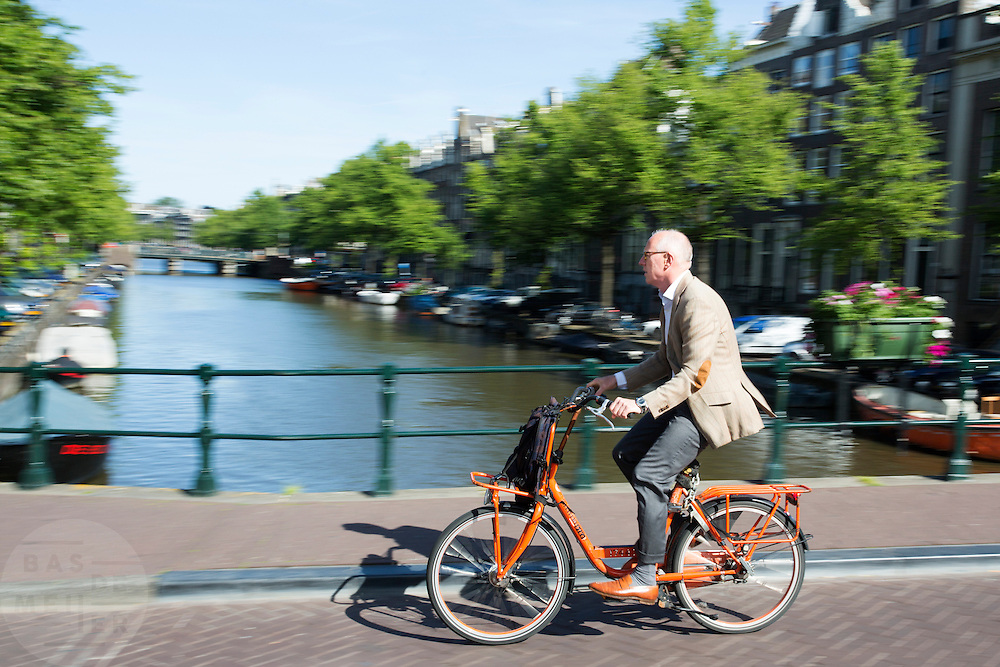 In Amsterdam rijdt een man in pak op een oranje fiets over de gracht.<br /> <br /> In Amsterdam a man in suit rides on an orange bike at the canals.