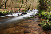 An area of clam water, with a section of fast flowing water beyond in the main flow of Horner Water on Exmoor.