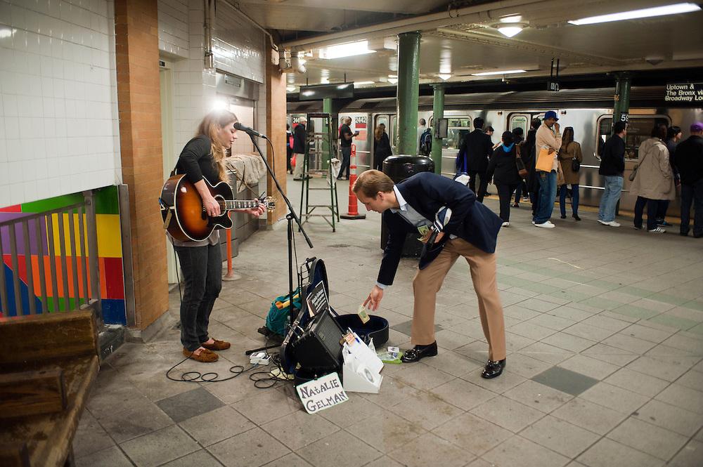 Natalie Gelman, 25, Saengerin und Songwriter mit Guitarre, begeistert mit Talent und Ausstrahlung. Sie ist offiziele Musikerin von 'Music Under New York'...Jedes Jahr im Mai laden die Betreiber der New Yorker Subway (MTA) ca 60 Musiker und Gruppen zu einem Wettberwerb im Grand Central Station ein. Die Gewinner duerfen ganz legal an ihnen zugeteilten Orten im Ubahn System auftreten. Viele unangemeldete  und selbst organisierte Musiker jeder nur erdenklichen Musikrichtung spielen zudem in fast jeder wichtigen Ubahnstation. Die Angst vor der Polizei ist dabei gering, selten gibt es eine Verwarnung und noch seltener ein Bussgeld. Meist wird einfach der Ort gewechselt falls es Probleme gibt...Natalie Gelman, 25, singer songwriter, draws crowds with her talent and enthusiasm. She is a participant of 'Music Under New York'...MTA (Metropolitan Transportation Authority) .Music Under New York.Auditions.Every Spring, Music Under New York (MUNY) presents a day of auditions in Grand Central Terminal to review and add new performers to the MUNY roster. This year, MUNY held its annual auditions in May on the Northeast Balcony of the Grand Central Terminal. .In addition legions of non-official musicians play in New Yorks subway stations and on platforms. One can find every thinkable style and instrument underground. ..Foto: Stefan Falke.