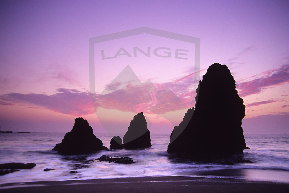 rock formations are silhouetted against a pink and purple sunset sky at rodeo beach in the marin headlands of golden gate national recreation area, san francisco, california.