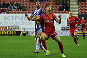 Wigan Striker Will Grigg battles with Aaron Morris (Gillingham)during the Sky Bet League 1 match between Wigan Athletic and Gillingham at the DW Stadium, Wigan, England on 7 January 2016. Photo by Pete Burns.