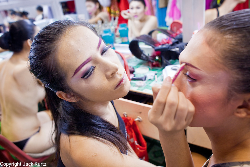 "Oct. 7, 2009 -- BANGKOK, THAILAND: ""Ladyboys"" help each other put their makeup on backstage at the Mambo Cabaret in Bangkok, Thailand. The performers at the Mambo Cabaret in Bangkok, Thailand are all ""Ladyboys,"" or kathoeys in Thai. Recognized as a third gender, between male and female, they are born biologically male but live their lives as women. Many kathoey realize they are third gender in their early teens, some only as old 12 or 13. Kathoeys frequently undergo gender reassignment surgery to become women. Being a kathoey in Thailand does not carry the same negative connotation that being a transgendered person in the West does. A number of prominent Thai entertainers are kathoeys. Photo by Jack Kurtz / ZUMA Press"