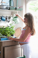 Pregnant woman watering house plants