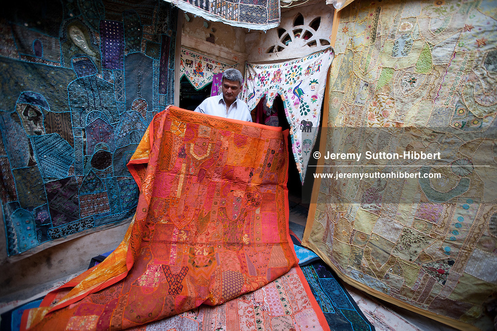 Carpet and textile merchant seller showing off his wares in Jaisalmer Fort, in Rajasthan, India, on 23rd December 2011.