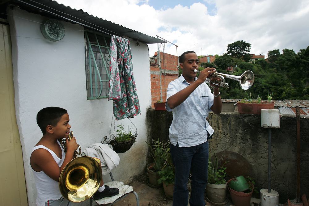 Wilfrido Galarraga, 21, and his nephew Onil Galarraga, 8, play instruments the roof of their home in La Vega, a poor shanty town on the outskirts of Caracas, Venezuela.  Wilfrido is part of the Venezuela Simon Bolivar Youth Orchestra, which is part of a music program encompassing more than 200,000 Venezuelan youth.  The program is meant to help underprivileged youth.