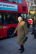Watched by a bus passenger, a gentleman walks along in Piccadilly, on 7th February 2018, in London, England.
