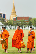 23 APRIL 2013 - BANGKOK, THAILAND:  Buddhist monks walk across Sanam Luang with the Grand Palace in the background. The palace has been the official residence of the Kings of Siam (and later Thailand) since 1782. The king, his court and his royal government were based on the grounds of the palace until 1925. The present monarch, King Bhumibol Adulyadej (Rama IX), currently resides at Chitralada Palace, but the Grand Palace is still used for official events. Several royal ceremonies and state functions are held within the walls of the palace every year. Construction of the palace began on 6 May 1782, at the order of King Buddha Yodfa Chulaloke (Rama I), the founder of the Chakri Dynasty, when he moved the capital city from Thonburi to Bangkok. Throughout successive reigns, many new buildings and structures were added, especially during the reign of King Chulalongkorn (Rama V). By 1925 the king, the Royal Family and the government were no longer permanently settled at the palace, and had moved to other residences. The palace complex is roughly rectangular and has a combined area of 218,400 square metres (2,351,000sqft), surrounded by four walls. It is situated on the banks of the Chao Phraya River at the heart of the Rattanakosin Island, today in the Phra Nakhon District. The Grand Palace is bordered by Sanam Luang and Na Phra Lan Road to the north, Maharaj Road to the west, Sanamchai Road to the east and Thai Wang Road to the south. The Grand Palace is made up of numerous buildings, halls, pavilions set around open lawns, gardens and courtyards. Its asymmetry and eclectic styles are due to its organic development, with additions and rebuilding being made by successive reigning kings over 200 years of history. It is divided into several quarters: the Temple of the Emerald Buddha; the Outer Court, with many public buildings; the Middle Court, including the Phra Maha Monthian Buildings, the Phra Maha Prasat Buildings and the Chakri Maha Prasat Buildings; the Inner Cou