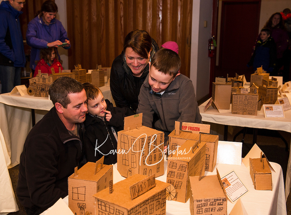 Sam Mize (far right) shows his family Michael, Jacob and Melissa Mize Mills made by his fellow 3rd graders during Elm Street School's presenation at the Belknap Mill Thursday evening. (Karen Bobotas/for the Laconia Daily Sun)