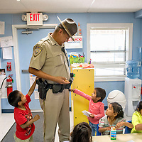 Headstart students inspect the gear of Ramah Navajo Police Officer Deirryck Clichee on a regular visit to Pine Hill School Monday.