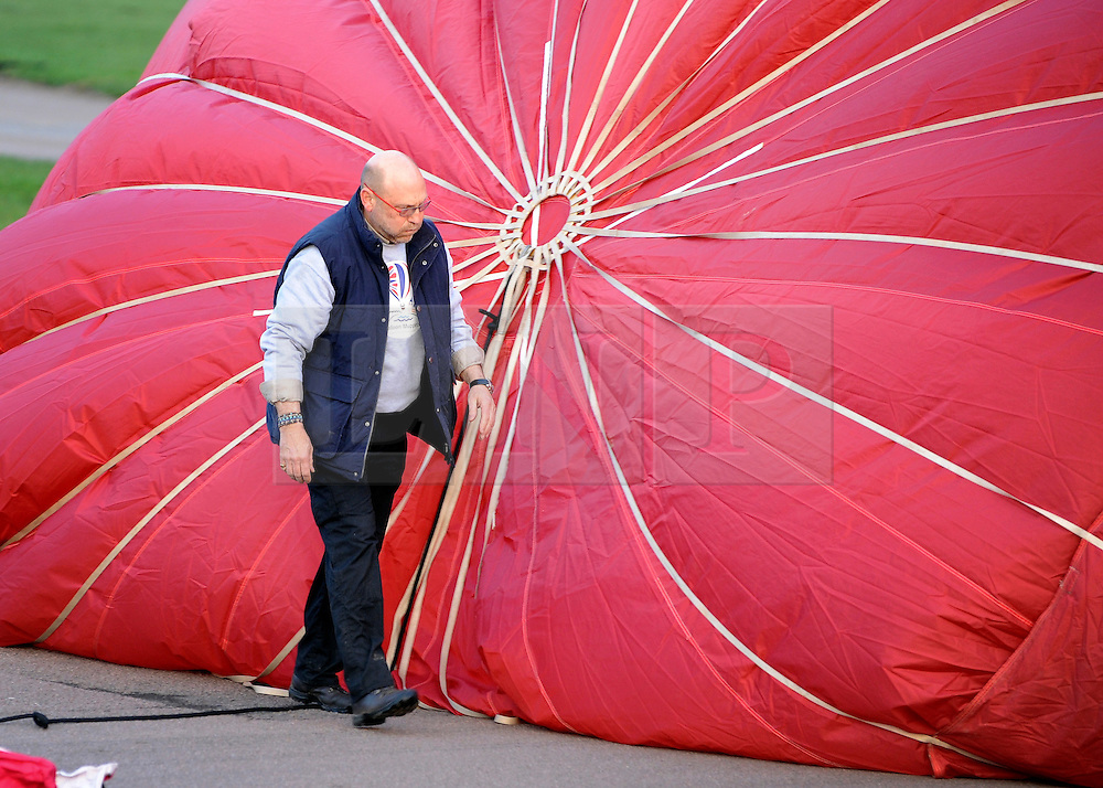©London News pictures. 07/04/2011. CANTERBURY: A flyer checks his balloon. Approximately 50 hot air balloons from across the UK and Europe take advantage of the weather window and take off from Lydden Hill Race Circuit, Wootton, Kent, to fly across the English Channel marking the largest ever group of balloons to attempt the crossing. The participants  have been waiting since October for the event to happen. Picture credit should read Stephen Simpson/LNP