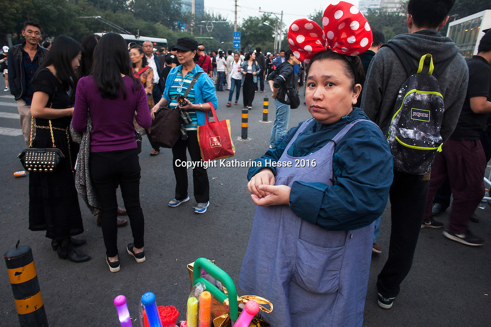 Sept.30, 2016 : a woman sells lightsticks outside the workers stadium before the 1986-2016 anniversary concert of China's most reknown rock musician Cui Jian. Cui came to fame in the late eighties, but was prohibited from performing in bigger venues for more than a decade due to his outspokenness in 1989 during the Tiananmen unrest.