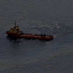 A vessel passes through oil on the surface of the water around the near the site of the Deepwater Horizon oil spill in the Gulf of Mexico near the coast of Louisiana, U.S., on Wednesday, June 2, 2010. BP Plc has given up trying to plug its leaking well in the Gulf of Mexico any sooner than August, laying out a series of steps to pipe the oil to the surface and ship it ashore for refining, said Thad Allen, the U.S. government's national commander for the incident. Photographer: Derick E. Hingle