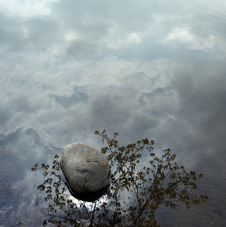 A boulder rests in the shoreline of Lake Nokomis.  The tranquil waters reflect the turbulent sky and a motionless tree while the sun attempts to reveal its presence.