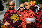 """13 JUNE 2013 - YANGON, MYANMAR:  Buddhist monks walk down a street in Yangon soliciting alms and donations. Most men in Myanmar join the """"Sangha"""" (clergy) at least once in their life. Some stay monks for just a few weeks, others for year and a few make it a life time commitment. Yangon, formerly Rangoon, is Myanmar's commercial capital and used to be the national capital. The city is on the Irrawaddy River and has a vibrant riverfront.    PHOTO BY JACK KURTZ"""
