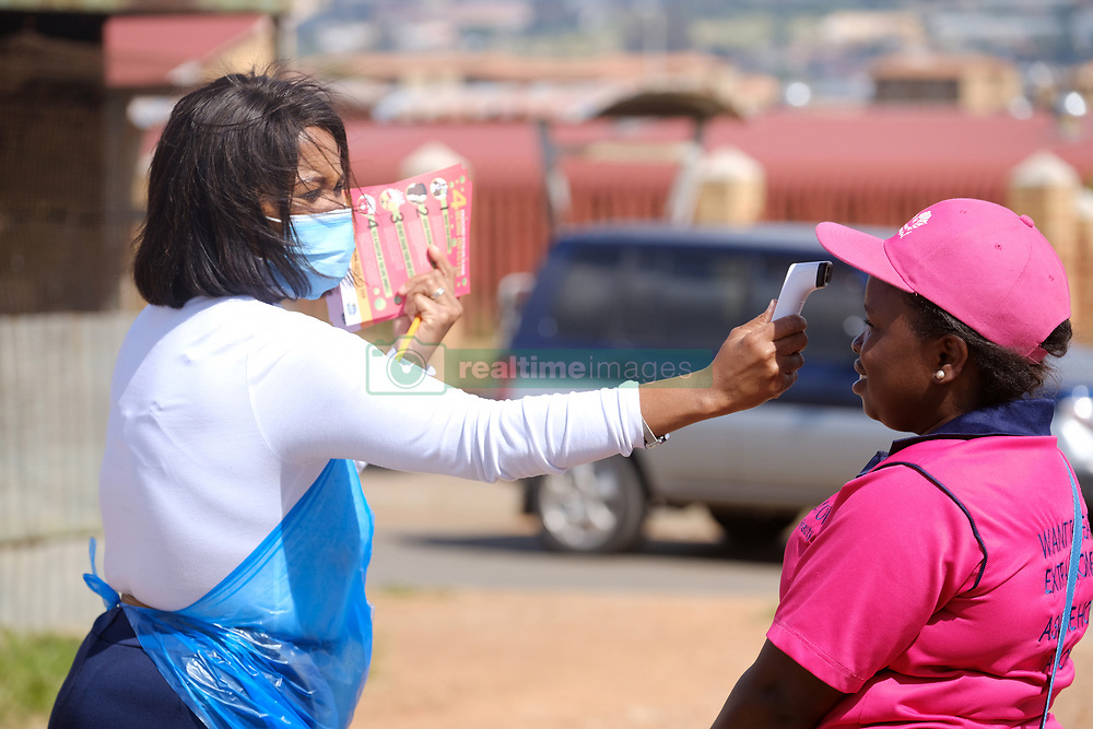 KRUGERSDORP, SOUTH AFRICA - APRIL 08: A health official takes the temperture of a member of the public at a Covid19 screening centre in the Munsieville suburb on April 08, 2020 in Krugersdorp, Mogale South Africa. Under pressure from a global pandemic. President Ramaphosa declared a 21 day national lockdown, mobilising goverment structures accross the nation to combat the rapidly spreading COVID-19 virus, or Coronavirus. The lockdown requires businesses to close and the public to stay at home during this period, unless part of approved essential services.(Photo by Dino Lloyd)