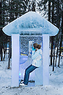 Teenager using functional phone in telephone booth carved out of ice at the 2008 World Ice Art Championships in Fairbanks, Alaska on March 13, 2008. MR.