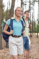 Happy young woman with man trekking in forest