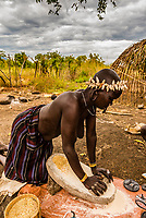 An older Mursi tribe woman using a grindstone to grind maize, Mago National Park, Omo Valley, Ethiopia.
