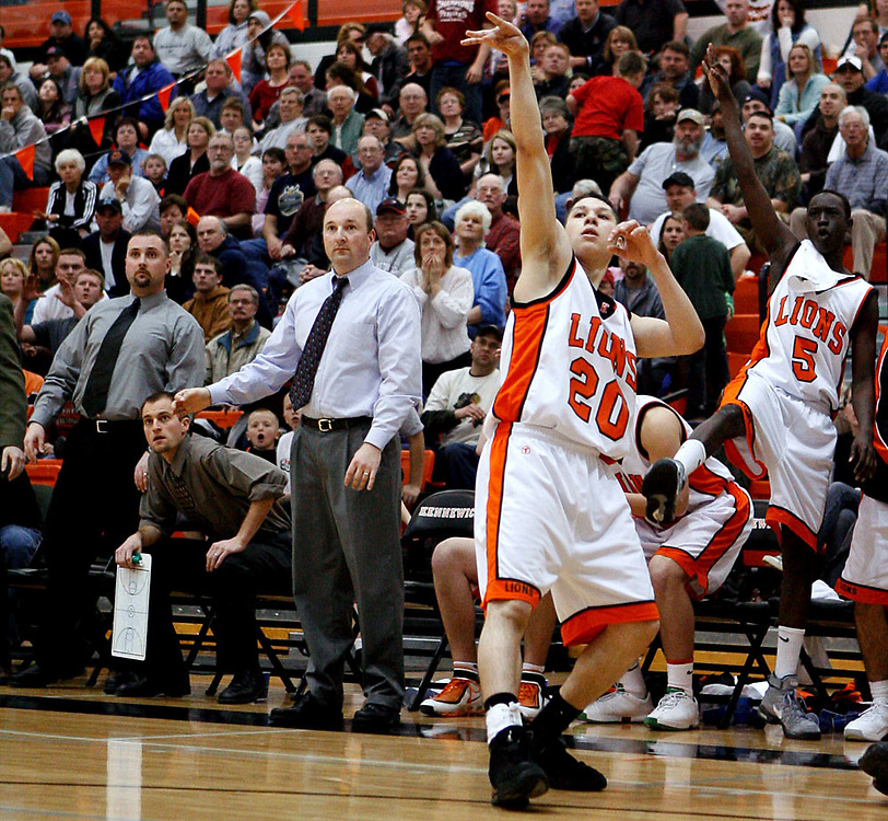 Kennewick's Osvaldo Uvay (20) shoots a three while teammate Kor Ter (5) hopes for the best from the bench during the Lions' 72-64 overtime win over Sunnyside on Wednesday.