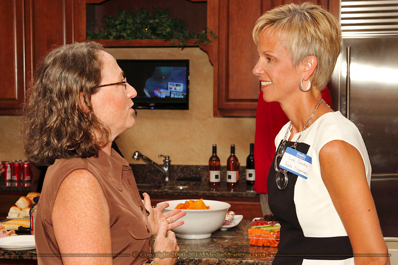 Bethany Schumacher of Konicki Schumacher Chiropractic (left) talks with Lori Firsdon of Forte Organizers during a Women in Business Networking After 5 event at Audio Etc... in Centerville, Thursday, August 30, 2012.