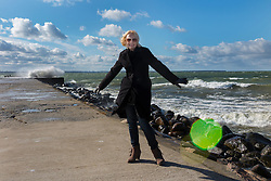 Woman standing on Merivälja pier in Tallinn. Stormy weather, Baltic sea.