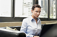 Businesswoman on Sofa Using Laptop