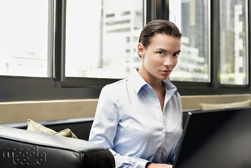 Businesswoman on Sofa Using Laptop