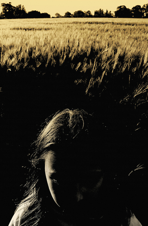 A young girl sitting in a golden cornfield
