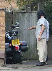 © Licensed to London News Pictures. 13/11/2015. London, UK.  Former Guantanamo detainee Shaker Aamer stands outside his home with an unidentified youth as they admire a neighbour's motorbike. Shaker Aamer was freed recently after being incarcerated in the US prison located in Cuba since 2002.  Photo credit: Peter Macdiarmid/LNP