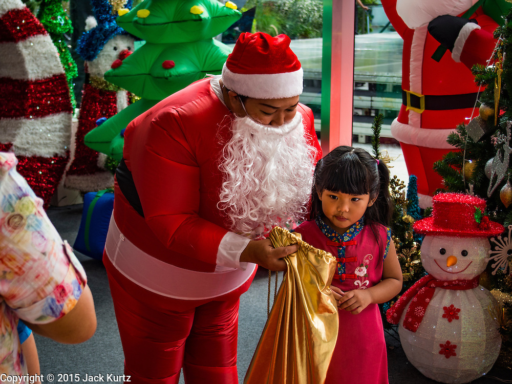 12 DECEMBER 2015 - BANGKOK, THAILAND: A Santa Claus wearing an inflatable Santa suit talks to children at EmQuarter, a new upscale shopping mall in Bangkok across Sukhumvit Road from Emporium, another Bangkok mall. Christmas in Thailand is a popular commercial / secular holiday.           PHOTO BY JACK KURTZ