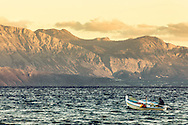 A Greek fisherman heading out to lay his fishing nets for tomorrows catch. Mirabello Bay with Ha gorge in the background, Lassithi Crete Greece.