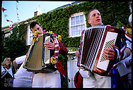 A couple of teenage accordionists play the traditional May Song during kids parade at Padstow's May Day festival; Cornwall, England.