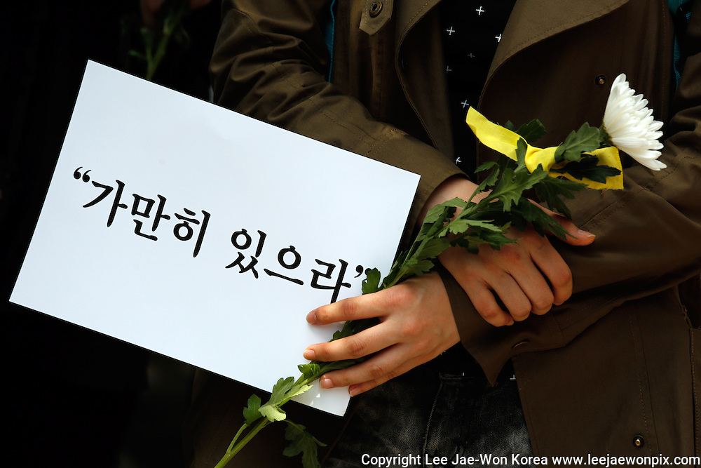 """A participant holds a sign and a flower during """"Stay Still"""" silent march against what they insist, lax response of President Park Geun-hye's government after the Sewol ferry was sunken in waters off the southwestern island of Jindo on April 16, 2014, on the street in Seoul, May 10, 2014. Signs read,""""Stay still"""", pasquinading captain of Sewol, who was broadcasting a message for passengers to wait until further notice, when the ferry was sinking, according to local media. Photo by Lee Jae-Won (SOUTH KOREA) www.leejaewonpix.com/"""