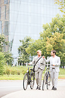 Businessmen talking while walking with bicycles on street