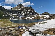 Two female hikers at the lake  Geisspfadsee, Landschaftspark Binntal, Valais, Switzerland
