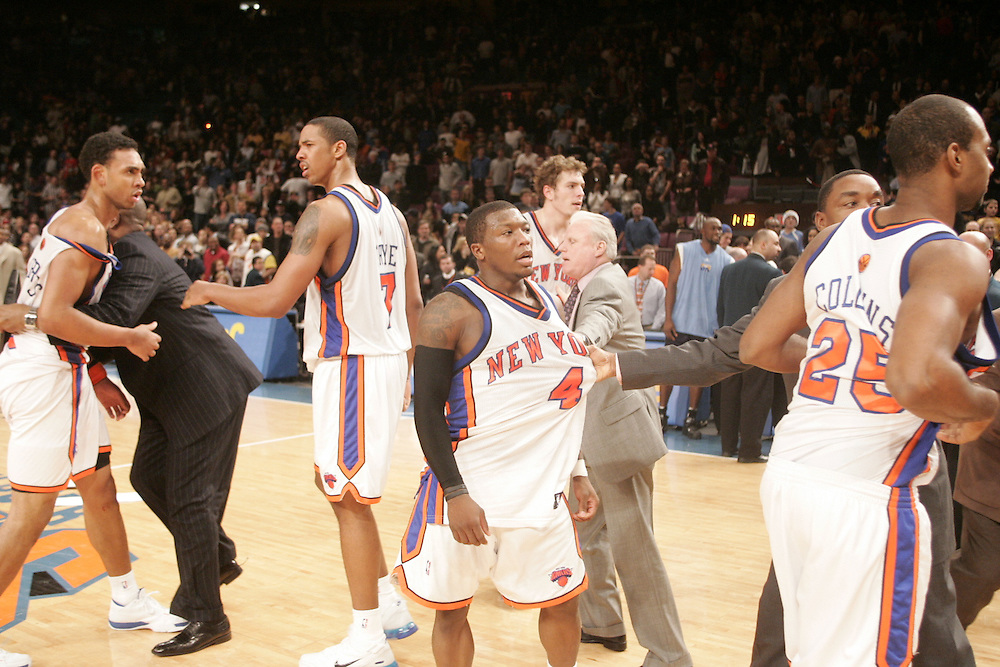 Nate Robinson and members of the New York Knicks are restrained by coachs and security during a fight with the Denver Nuggets at Madison Square Garden, New York on Saturday  16 December 2006. (Andrew Gombert for The New York TImes)