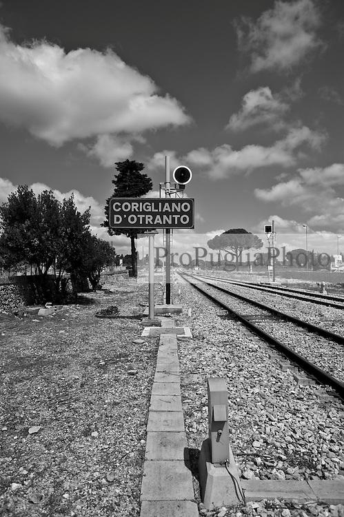 alla fine della banchina della stazione troneggia il  cartello indicante il nome della fermata. Reportage che analizza le situazioni che si incontrano durante un viaggio lungo le linee ferroviarie delle Ferrovie Sud Est nel Salento.
