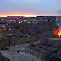 030414  Adron Gardner/Independent<br /> <br /> A Berlington Northern/Santa Fe train passes by a brush fire smoldering adjacent to the Puerco canal in Gallup Wednesday.