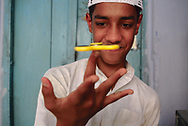 Student of a madrasa at a small mosque in Old Delhi doing tricks with a fidget spinner