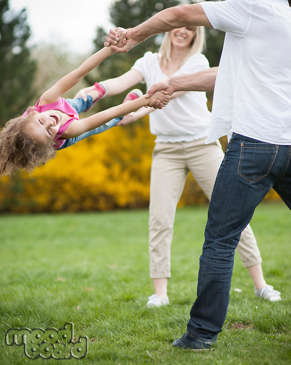 Young couple swinging daughter between them