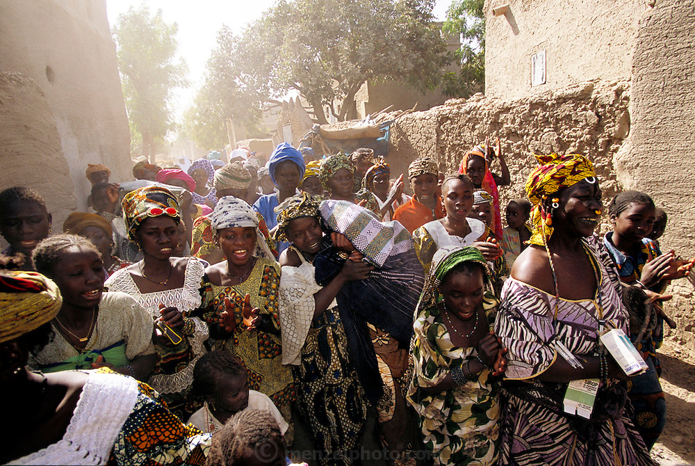 Earlier this morning, 18-year-old Pai somberly contemplated what she had just learned: later today she was to formally wed her first cousin, Baba Nientao, and then move to his home in Ivory Coast. None of the parents attend the ceremony. Instead, Pai's girlfriends raucously lead her (hidden under a shawl, shown here) to the Town Hall, where she and Baba sign their marriage license alone with the mayor. Hungry Planet: What the World Eats (p. 215). The Natomo family of Kouakourou, Mali, is one of the thirty families featured, with a weeks' worth of food, in the book Hungry Planet: What the World Eats.