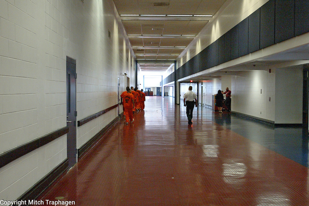 A group of prisoners walk single file down a long hallway in the Orient Road Jail in Tampa, Florida