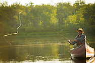 Woolrich Summer and Spring in Maine. 2016 of fly fisherman in red canoe at sunrise casting a fly on a calm lake in Maine
