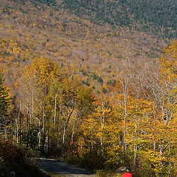 A man mountain biking on a logging road near Grafton Notch State Park in Maine's Northern Forest.  Old Speck is in the distance. MR