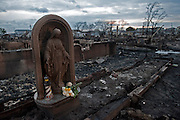 Statue of the Virgin Mary sits amongst the rubble of 111 homes that burned completely to the ground in Breezy Point, Queens. Jonah Markowitz/Falcon Photo Agency