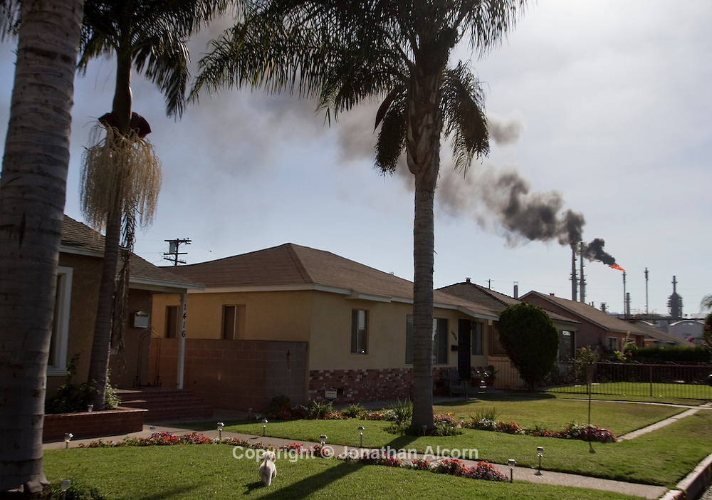 A row of homes on a residential street stands as black smoke from a flair fills the air as the ConocoPhilips Refinery in the Wilmington section of Los Angeles performed a non- emergency burn-off caused by a power outage and that shut down the oil refinery. The incident did not require a response from emergency personnel according to fire department officials.